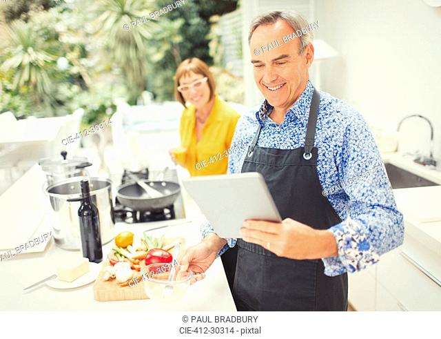 Mature couple with digital tablet cooking in kitchen