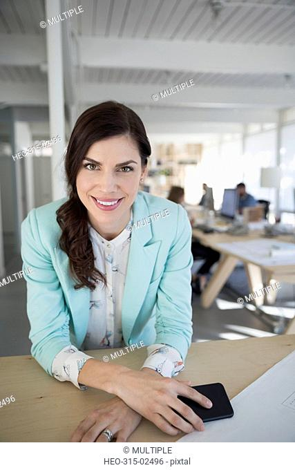 Portrait smiling female architect with cell phone in office
