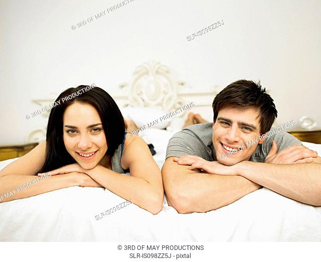 Young couple lying on bed, portrait