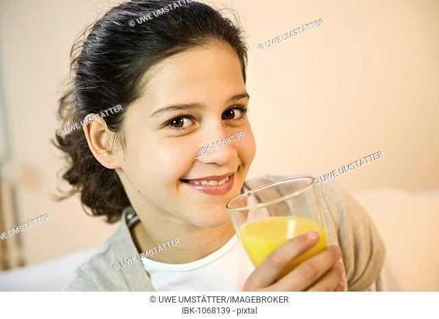 Girl drinking a glass of orange juice