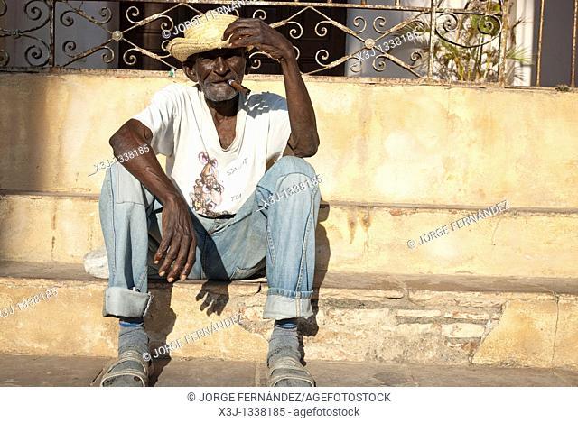 Old man with a cigar sitting down in the street, Trinidad, Sancti Spiritus, Cuba, Caribbean