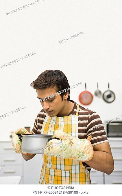 Man smelling a cooking pan
