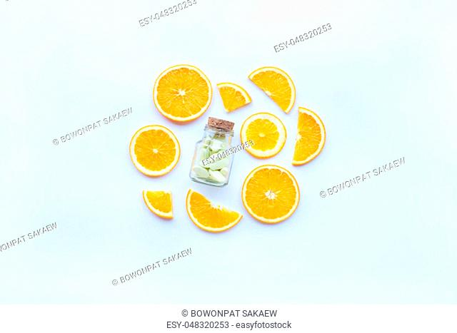 Vitamin C bottle and pills with orange fruit slices on white background