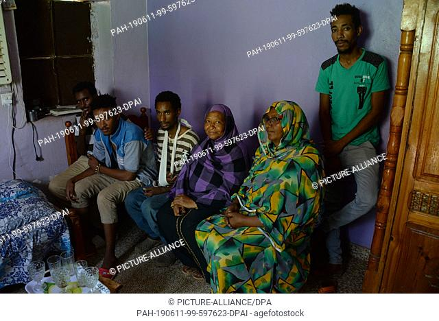 10 June 2019, Sudan, Khartum: Ali Idris (l-r), Amar Mohammed al-Hassan and Abdu al-Rahim sit with other family members in one room