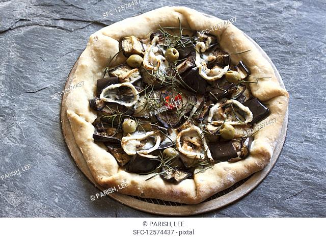 Pizza topped with eggplant, goat's cheese, rosemary, red pepper and green olives