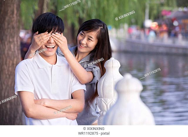 Woman Covering Mans Eyes by a Lake