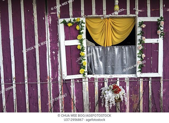 A Malay house with a wooden window panel next to a mosque in Kuching city centre, Sarawak, Malaysia