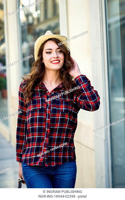 Young woman with beautiful blue eyes wearing plaid shirt and sun hat. Girl smiling in urban background