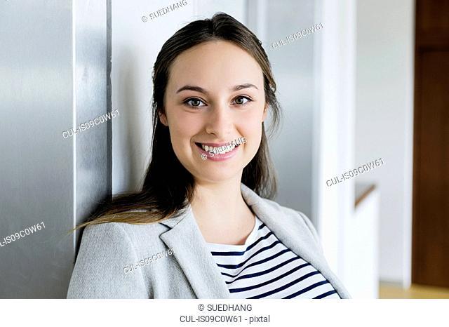 Businesswoman leaning against elevator door