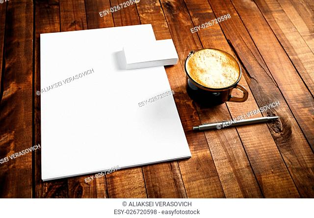 Photo of blank stationery set. Corporate identity template on vintage wooden table background. Letterhead, business cards, coffee cup and pen