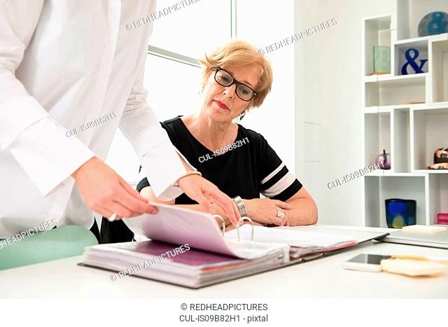 Businesswomen looking at files at desk