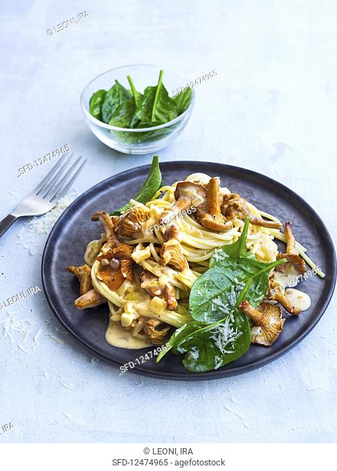 Spaghetti with chanterelle mushrooms and a creamy sauce served with a spinach salad