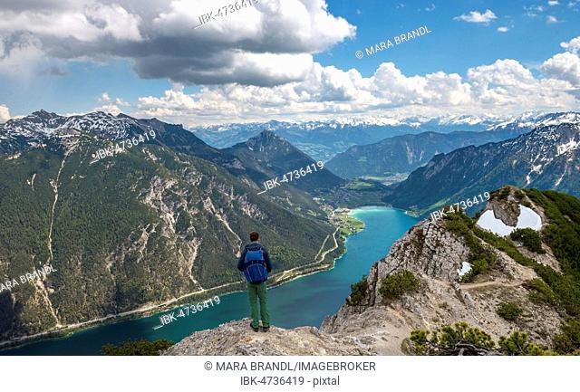 Hiker on hiking trail, crossing from the Seekarspitz to the Seebergspitz, view over the lake Achensee, Tyrol, Austria