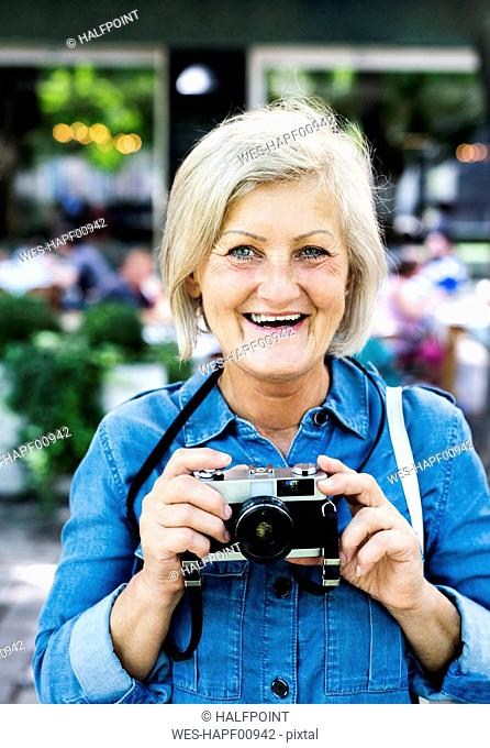 Portrait of happy senior woman with camera