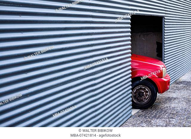 Portugal, Azores, Sao Miguel Island, Ponta Delgada, corrugated steel wall with car