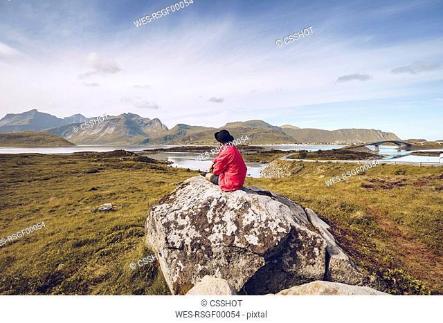 Norway, Lofoten, man wearing red rainjacket sitting on a rock looking at view