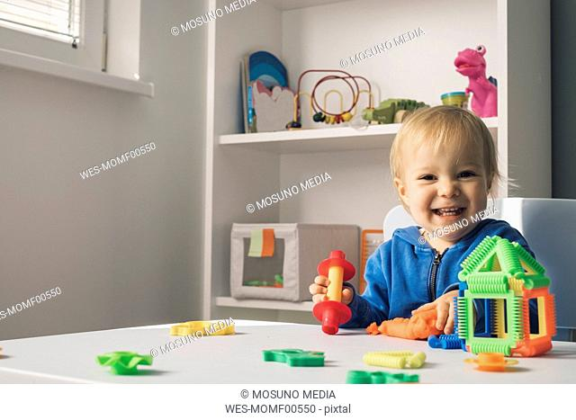 Portrait of laughing baby girl playing with modeling clay in children's room