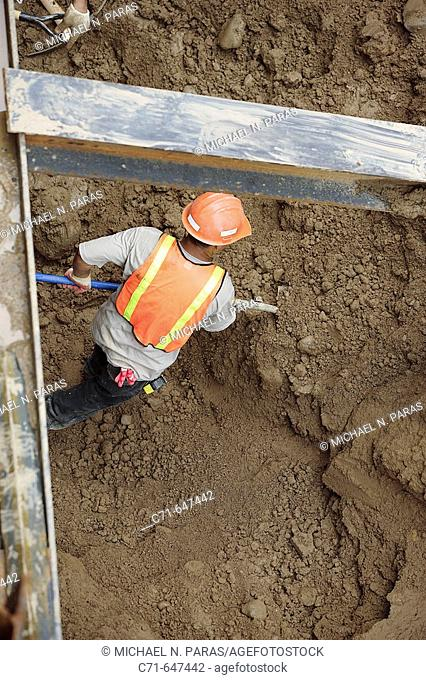 Construction worker shoveling dirt in pit