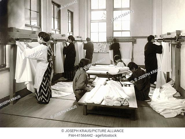 Fabrics of silk are folded in a special measure fixture. Pictured in the early 1920th. - /Japan