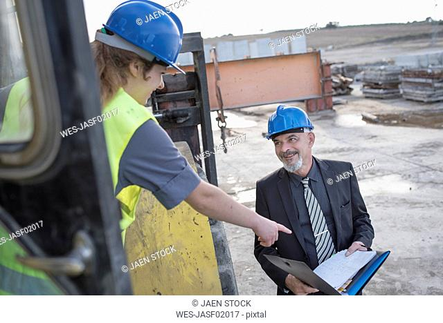 Businessman talking with female worker on bulldozer on construction site