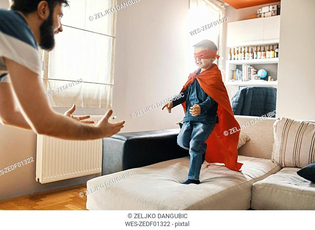 Father playing with his little son dressed up as a superhero at home