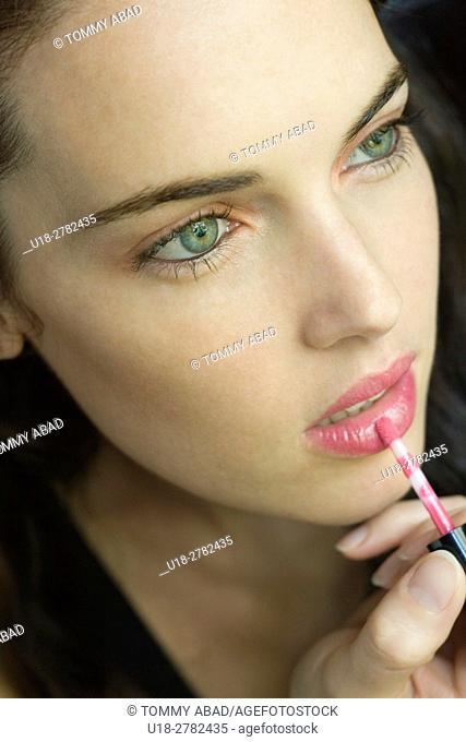 a beautfil brunette woman puting lipgloss in her lips
