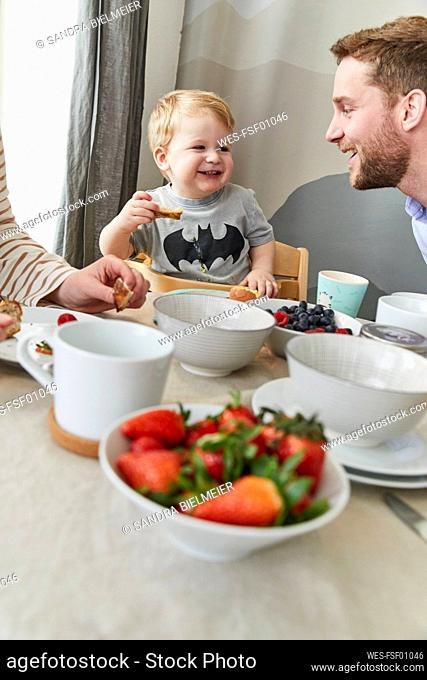 Portrait of happy little boy having fun at breakfast table with his father