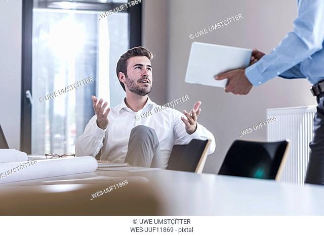 Businessman sharing tablet with colleague in office
