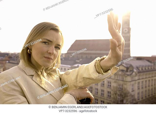fancy blogger woman stretching arm on balcony next to church Frauenkirche, Marienkirche, in Munich, Bavaria, Germany
