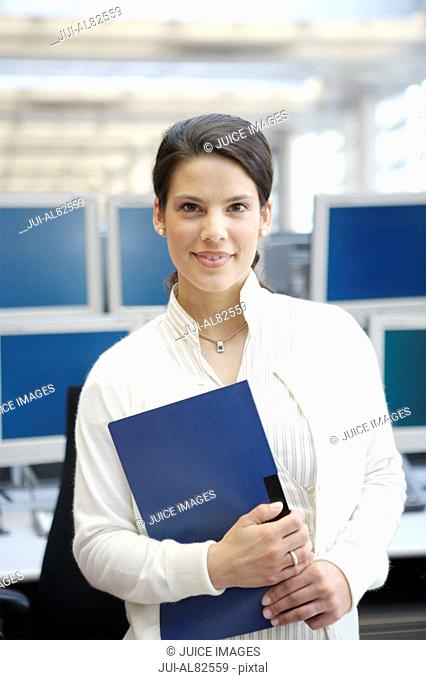 Businesswoman smiling and holding binder in office
