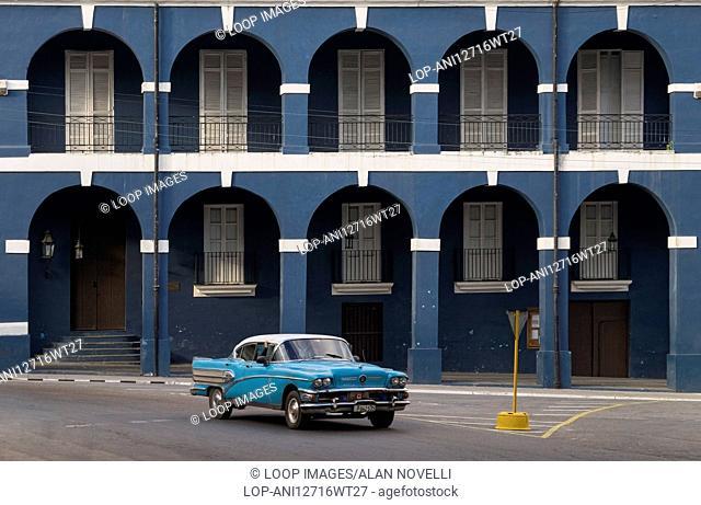 An old American 1950s blue Cuban car passing Museo Historico Provincial de Matanzas