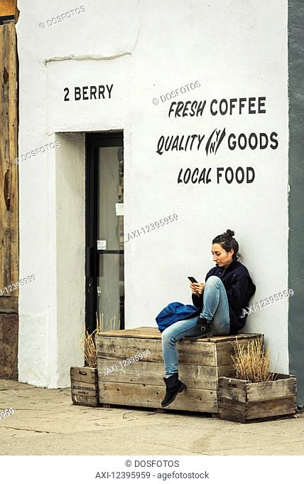 Young woman using her smart phone outside a coffee shop in Williamsburg; Brooklyn, New York, United States of America