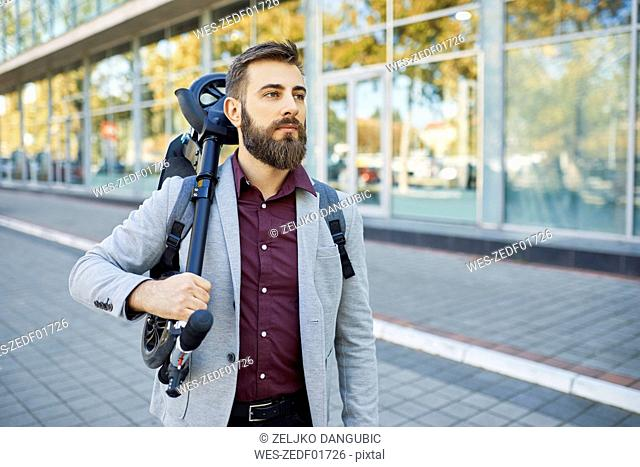 Businessman carrying scooter