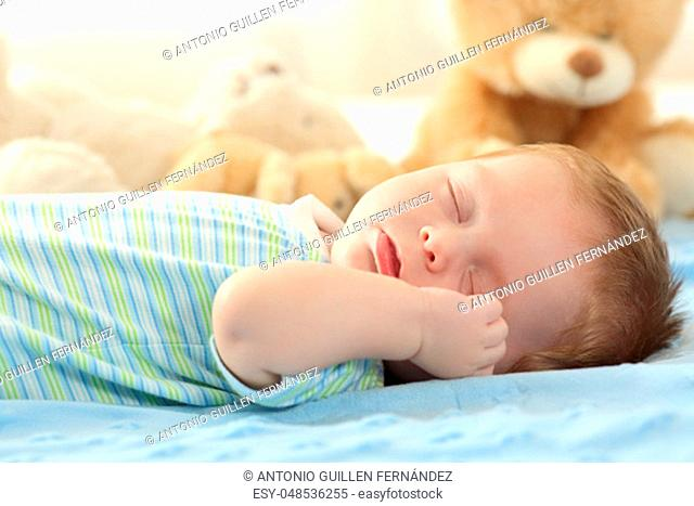 Portrait of a cute baby sleeping on a bed