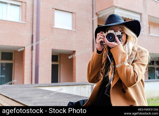 Young woman in hat filming through camera against building