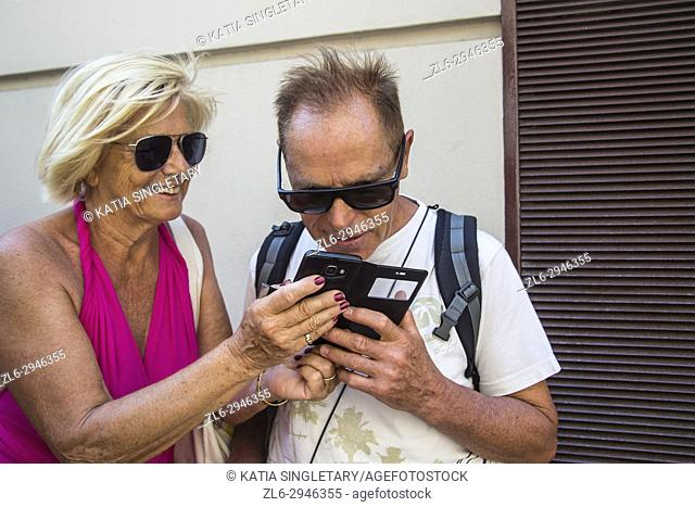 Older senior retired caucasian couple with a phone trying to get to know how to use it. They are laughing and speaking on speakerphones