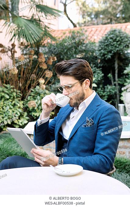 Elegant businessman drinking coffee and using tablet in a garden cafe