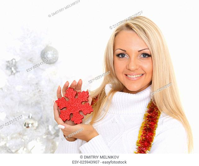Young happy beautiful woman in winter clothes with snowflake stands near Christmas tree on a white background