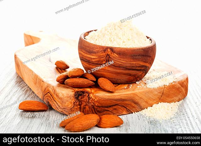Almond flour and almonds on wooden cutting board