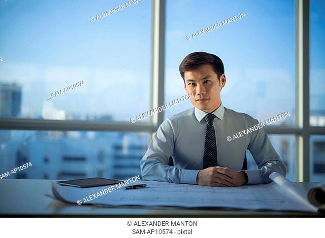 Singapore, Indoor portrait of architect at desk with building plans