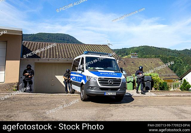 13 July 2020, Baden-Wuerttemberg, Oppenau: Officers and a police vehicle are standing to cordon off a scene in a residential area