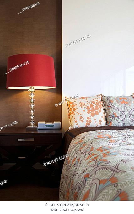 Nightstand and Lamp Next to a Bed