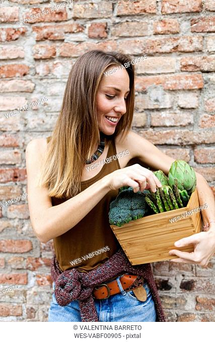 Smiling woman holding bix with fresh vegetables