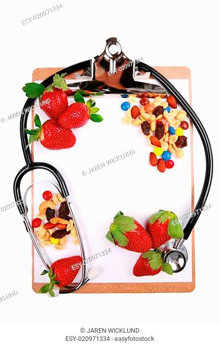 Fruits and nuts on clipboard with stethoscope
