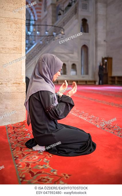 Muslim woman in headscarf and hijab prays with her hands up in air in mosque. Religion praying concept