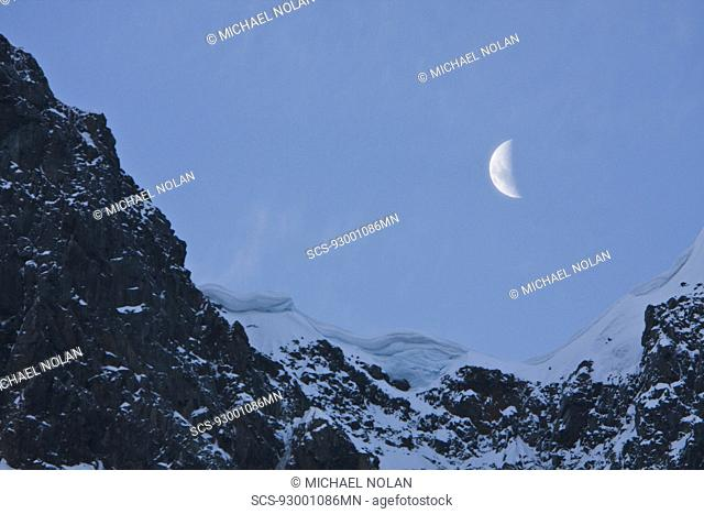 A quarter moon setting over the scenic Lemaire Channel on the west side of the Antarctic peninsula in Antarctica