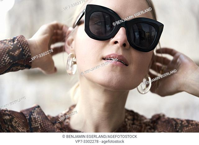 fashionable woman wearing stylish plastic earrings, in Munich, Germany