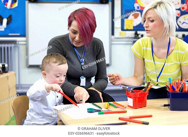 Nursery teacher sitting with a parent and her Down Syndrome son in the classroom. they are discussing the little boys progress
