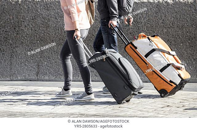 Young couple with wheeled suitcases at airport