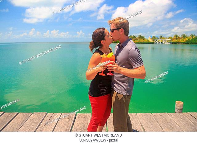 Romantic couple kissing on waterfront pier, St. Georges Caye, Belize, Central America
